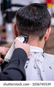 Hairdresser cutting hair to a client with an electric machine