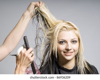 Hairdresser cutting hair of woman of smiling girl