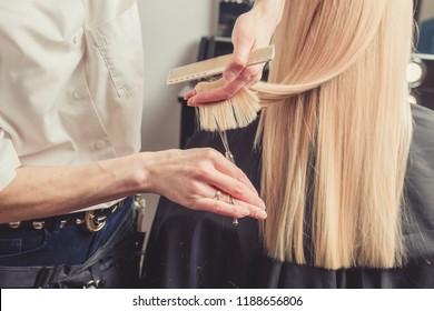 Hairdresser is cutting long blond hair in hair salon