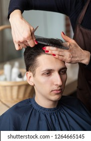 Hairdresser cutting man's hair with scissors. hairdresser getting a new haircut