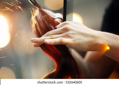 Hairdresser cutting and modeling brown hair by scissors and comb