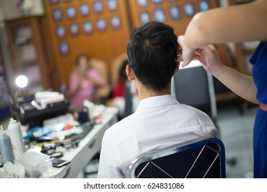 The hairdresser is design the hair to the groom on the wedding ceremony day