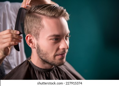 hairdresser  does   hair  with black comb of handsome satisfied  client in  professional  hairdressing salon