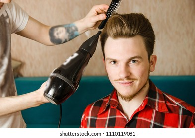 Hairdresser does hair styling pompadour to a young man