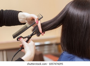 The hairdresser does a haircut with hot scissors of hair to a young girl, a brunette in a beauty salon.
