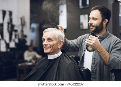 The hairdresser does a hairstyle to an old man with gray hair in a barbershop. The stylist uses scissors, combs, a sprayer. A man is sitting in a chair.