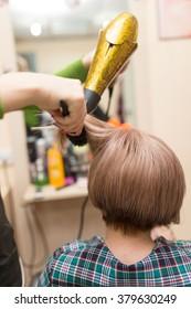 Hairdresser dries the hair dryer blond  hair