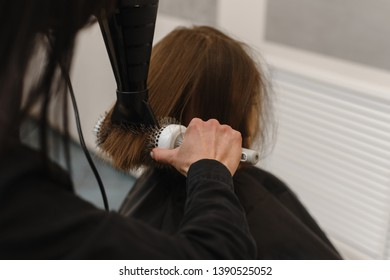 the hairdresser dries the wet hair with a hair dryer to the client. Beautiful beauty salon. Copyspace. The girl makes styling with a hair dryer and a round comb. The client sits in a chair and a black