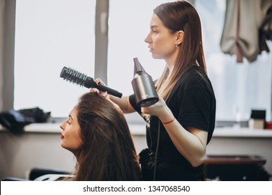 Hairdresser drying hair to a girl and doing her hairdo in a beauty salon