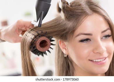 Hairdresser drying long brown hair with hair dryer and round brush. Close-Up.