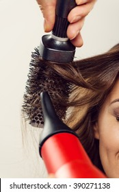Hairdresser drying long brown hair with round brush.