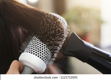 Hairdresser drying woman's hair with hair dryer and round brush in beauty salon, closeup