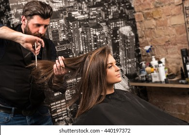 Hairdresser during work with beautiful woman client