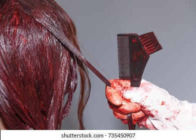 hairdresser dyeing hair color red in a beauty salon