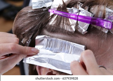 Hairdresser is dying female hair. Hair dying coloring foil