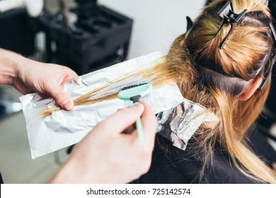 Hairdresser is dying female hair, making hair highlights to his client with a foil. Selective focus.