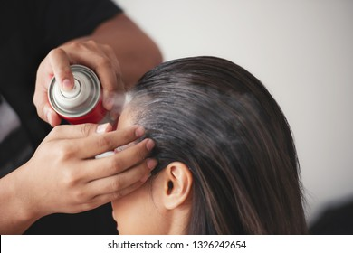 hairdresser fixing a coiffure with ringlets of a woman using a hair spray in a beauty salon. concept of professional stylist training