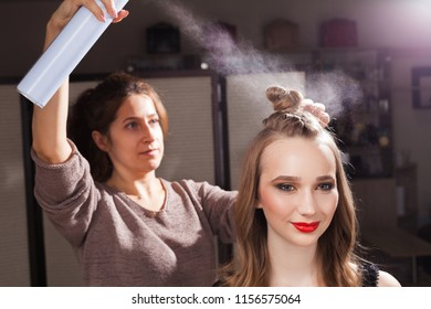 hairdresser fixing a coiffure with an unusual bun of a young beautiful girl using a hair spray in a beauty salon. concept of professional stylist studying