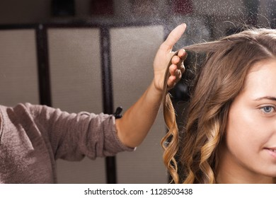 hairdresser fixing a coiffure with waves of a young beautiful girl using a hair spray in a beauty salon. concept of professional stylist studying