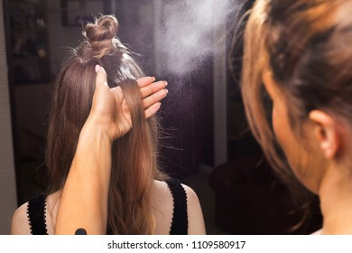 hairdresser fixing hair of a young beautiful model with a coiffure using a hairspray in a beauty salon. concept of professional stylist studying
