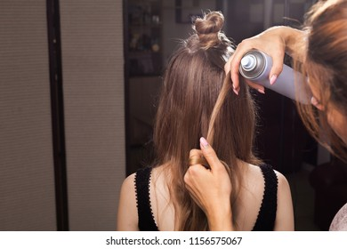 hairdresser fixing hairstrand of a young beautiful model with a coiffure using a hairspray in a beauty salon. concept of professional stylist studying