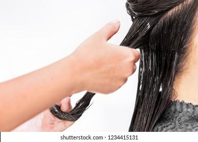 hairdresser hair treatment. applying color cream at hair.