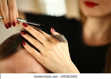 Hairdresser Hands Holding Scissors and Hairbrush. Female Hands Trimming Male Hair. Fingers with Red Manicure Cutting Hairdo. Hairstylist Making Haircut for Man Closeup. Hairstyle Partial View Photo