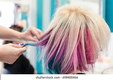 Hairdresser holding cowlick of client colored hair and making haircut in beauty salon. Fresh colored rainbow hair.