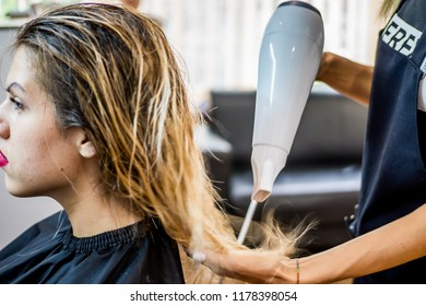 The hairdresser makes the client in the beauty salon make-up of hair with natural ingredients and vitamins, restores the tips of the hair, blows her hair after washing her hair