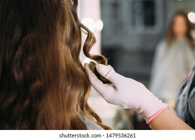 the hairdresser makes curls to the client, the female hand holds hair. beauty salon, training l
