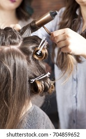 A hairdresser makes curls with a iron and hair clips