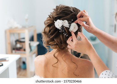 hairdresser makes an elegant hairstyle styling bride with white flowers in her hair in the salon