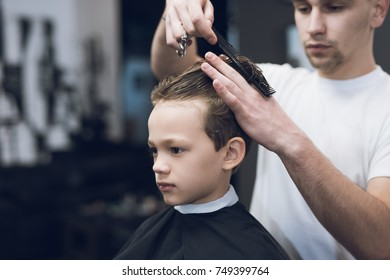 The hairdresser makes a fashionable pretty hairstyle for the boy in a modern barbershop. The stylist uses a comb, scissors, a clipper.