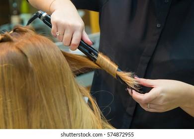 Hairdresser makes hair perm