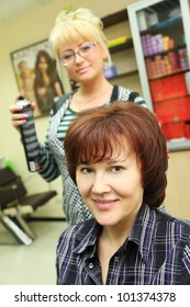Hairdresser makes hair styling for woman by hair spray in beauty salon; focus on happy client