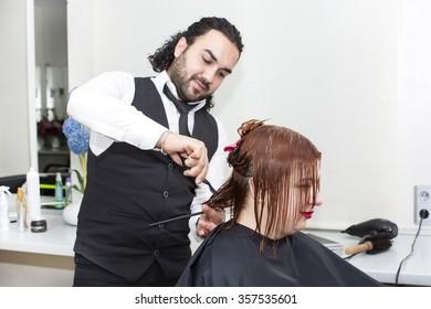 Hairdresser makes hair woman in a beauty salon