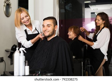 Hairdresser makes the haircut for man in the hairdressing salon