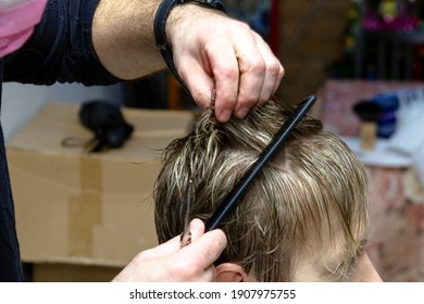 The hairdresser makes a haircut to a young woman at home.