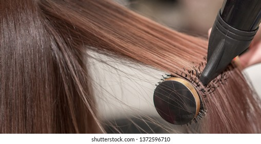 Hairdresser makes hairstyle client. Hair styling with a hair dryer and comb, hair straightening in a beauty salon. Beautiful silky smooth hair.