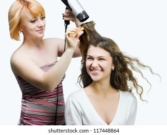 Hairdresser makes hairstyle for young pretty women