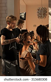 Hairdresser and make-up artist works in a beauty salon with a beautiful young asian woman a client. Preparing the model around mirror- to do hair and makeup at the same time backstage- stock photo.