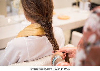 Hairdresser making a braids to a woman client in a beauty salon