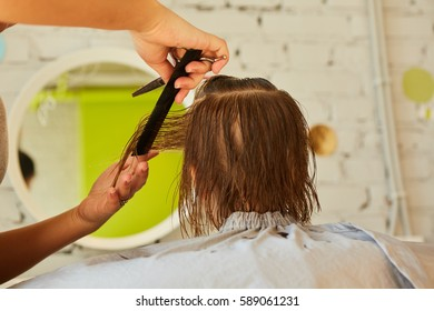 Hairdresser making a hair style to cute little girl.