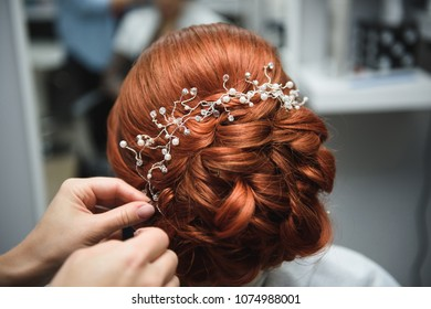 hairdresser making hairstyle for red hair bride