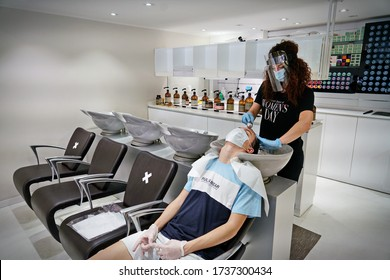 Hairdresser with mask and gloves washing the client's hair with soap. Reopening with security measures of Hairdressers in the Covid-19 pandemic. Turin, Italy -May 2020