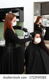 hairdresser in a medical mask works in the salon