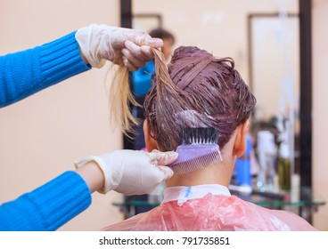 The hairdresser paints the woman's hair in white, apply the paint to her hair in the beauty salon.