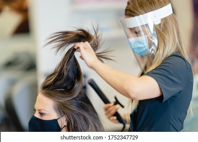 Hairdresser, protected by a mask, making waves in her client's hair with a hair iron in a salon. Business and beauty concepts