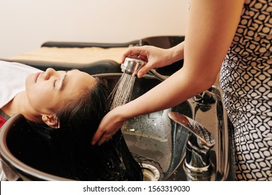 Hairdresser rinsing hair of female customer with water after using shampoo and conditioner