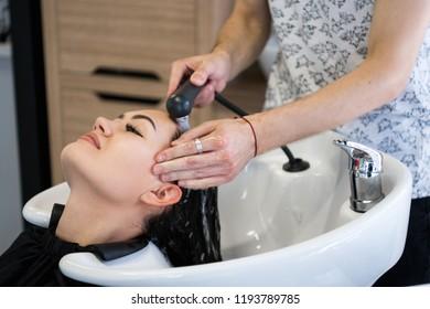 Hairdresser salon. Beautiful brunette woman during hair wash